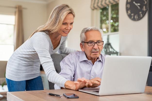 Filha, ajudando o velho pai com laptop