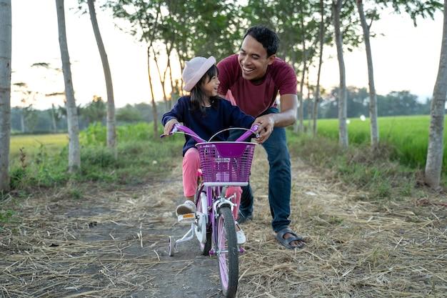 Filha aprendendo a andar de bicicleta com o papai