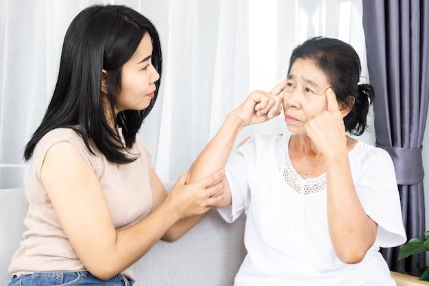 Filha asiática ajudando e apoiando sua mãe idosa com o problema da doença de alzheimer