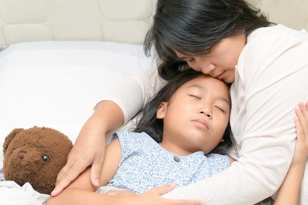 Filha asiática bonita, abraçando a mãe antes de dormir