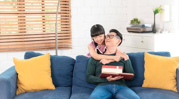 Filha asiática dá um presente para o pai. conceito caixa de presente surpresa para o dia dos pais.