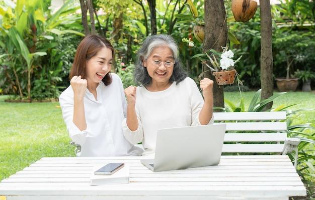 Filha asiática ensinando uma mulher idosa a usar a mídia social on-line no laptop após a aposentadoria.
