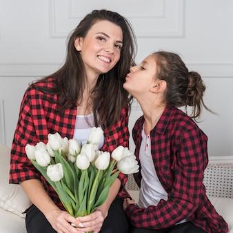 Filha beijando a mãe com tulipas