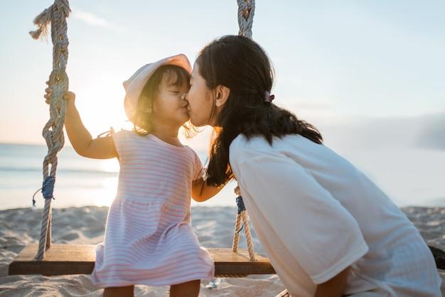 Filha beijando a mãe enquanto balança na praia