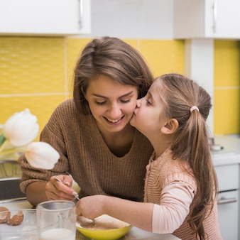 Filha beijando a mãe enquanto cozinha na cozinha