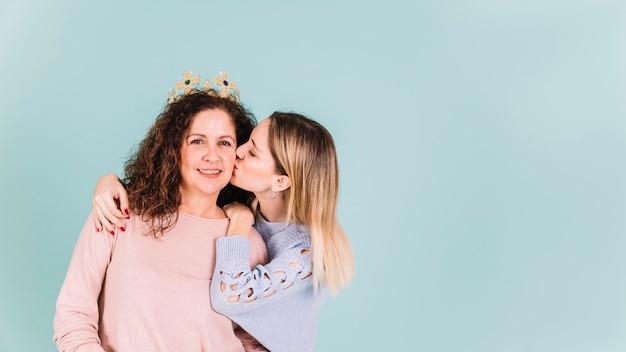 Filha beijando a mãe na coroa