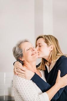 Filha beijando a mãe no dia das mães