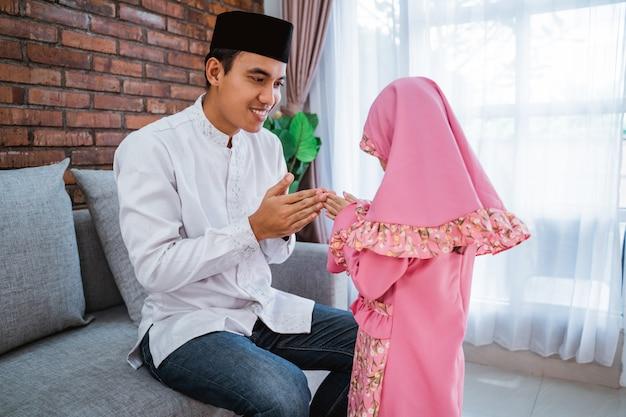 Filha beijando as mãos para seu pai no eid mubarak