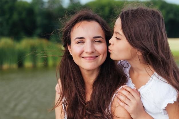 Filha, beijando, feliz, mãe, por, a, lago