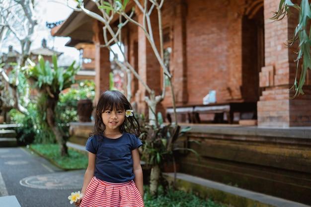 Filha bonita vestindo flor de frangipani