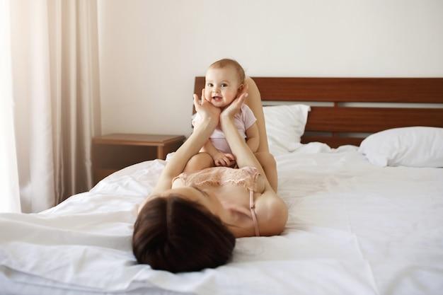 Filha bonito bebê agradável sentado em sua jovem mãe deitada na cama, sorrindo em casa.