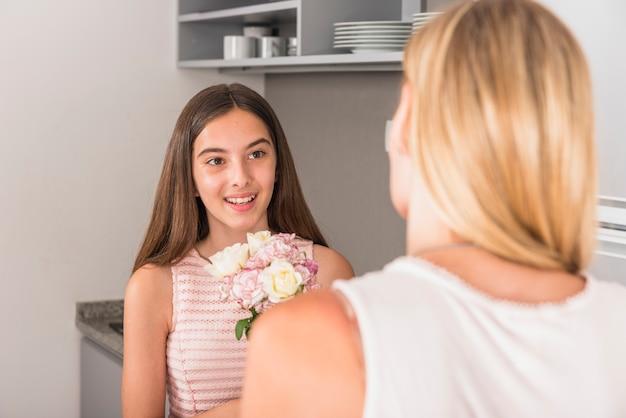 Filha bonito dando flores para a mãe na cozinha Foto gratuita