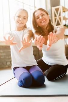 Filha bonito e mãe posando em tapetes de ioga