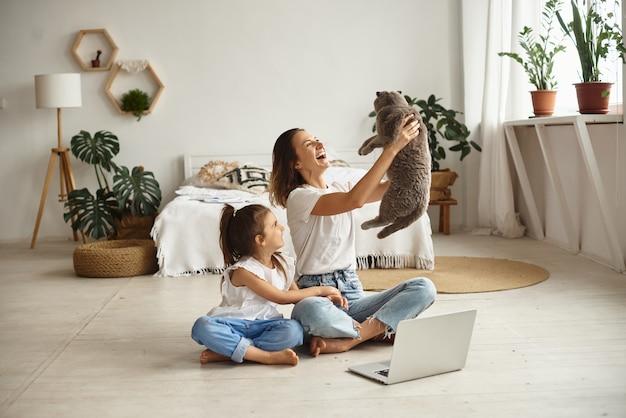 Filha brinca com a mãe e o gato enquanto a mãe trabalha no computador