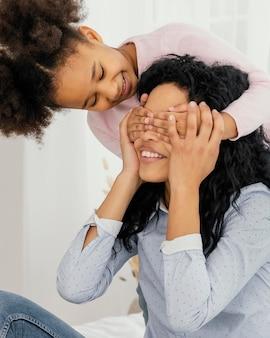 Filha brincando com a mãe em casa