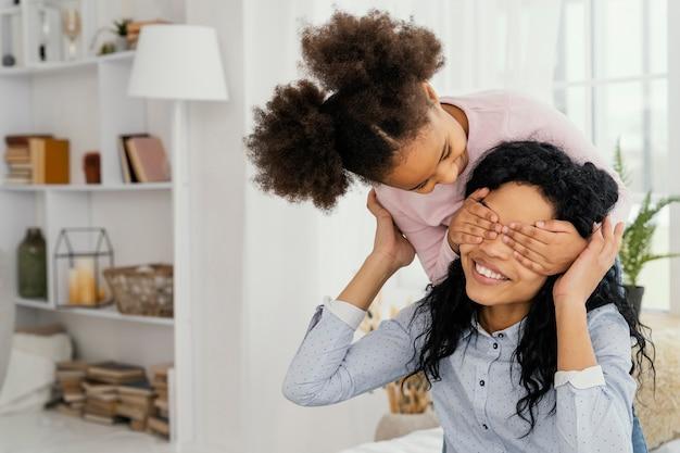 Filha brincando com a mãe sorridente em casa