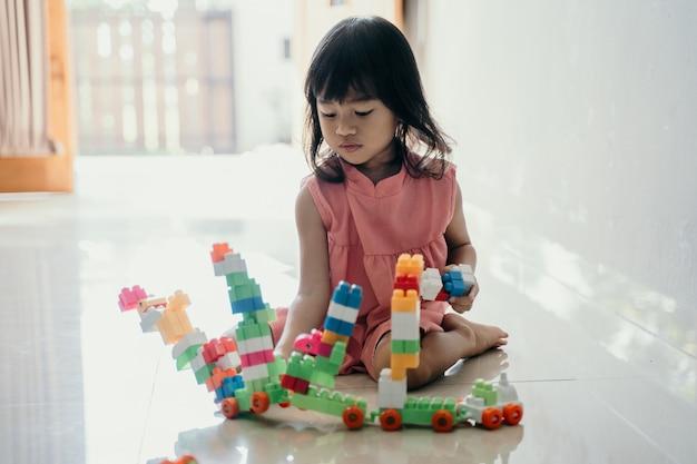 Filha brincando com tijolo plástico em casa