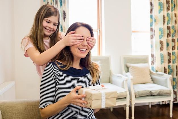 Filha cobrindo os olhos da mãe na sala de estar