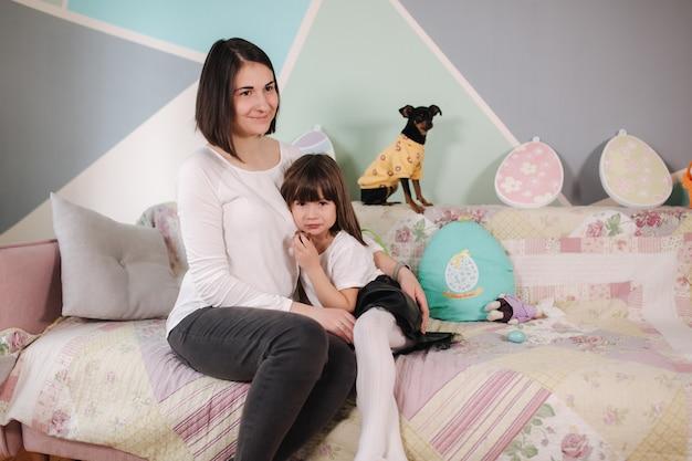 Filha com a mãe brincar com o cachorro em casa família feliz se preparando para a páscoa