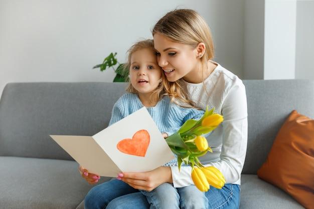 Filha com buquê de flores amarelas e cartão postal parabeniza mãe sorridente