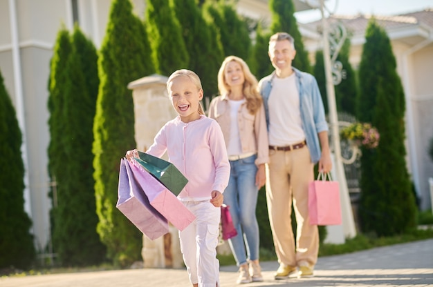Filha com compras e pais abraçados atrás Foto Premium