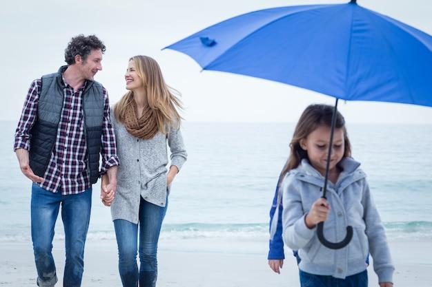 Filha com guarda-chuva enquanto os pais caminhando na beira-mar
