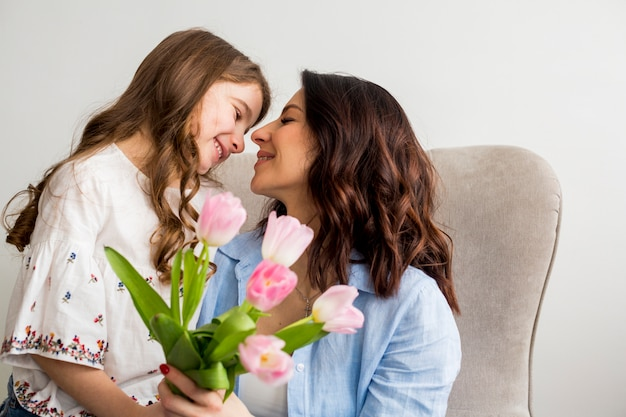 Filha com tulipas abraçando a mãe na poltrona