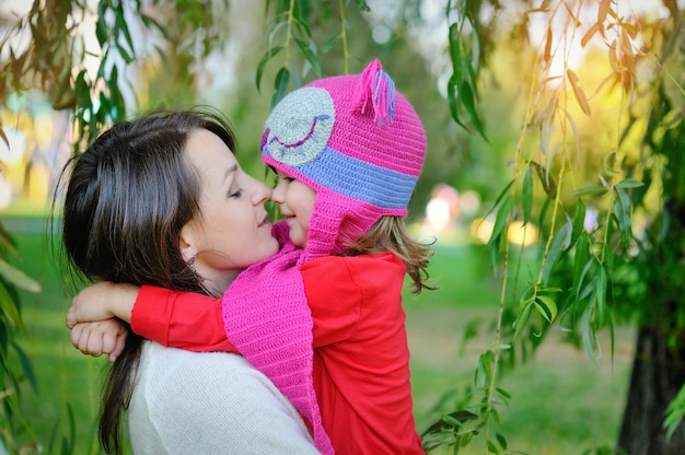 Filha com um boné de malha com sua mãe no parque.