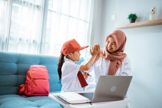 Filha com uniforme escolar e highfive com a mãe durante aula online em casa