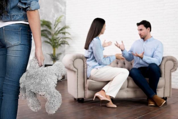 Filha com urso de pelúcia, olhando para os pais discutindo