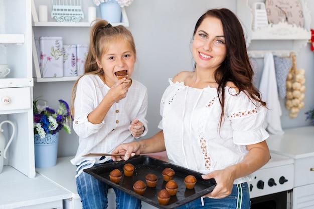 Filha comendo bolos e mãe segurando a bandeja