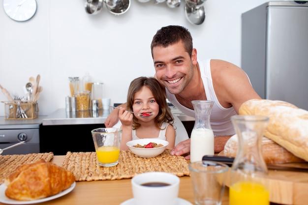 Filha comendo cereais e frutas na cozinha