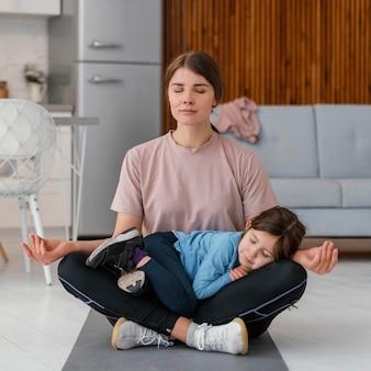 Filha completa, criança e mãe meditando
