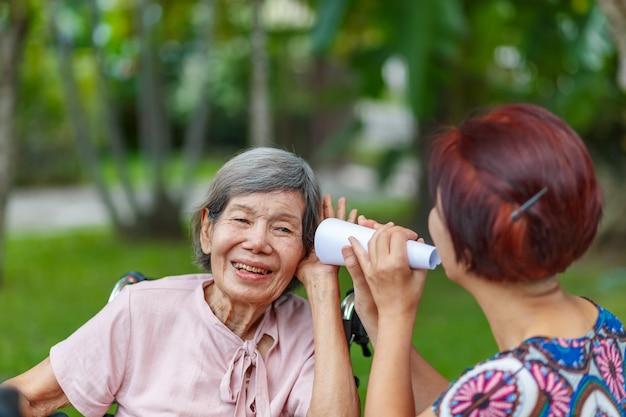 Filha conversando com mulher idosa com deficiência auditiva, usando tubo de papel