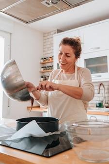 Filha cozinhando uma sobremesa de chocolate para dar à mãe no dia das mães