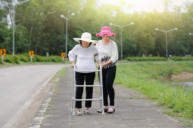 Filha, cuide de mulher idosa andando na rua sob forte luz solar.