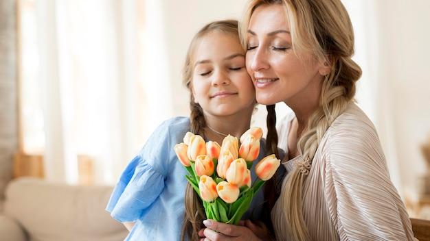 Filha dando buquê de flores para a mãe como presente
