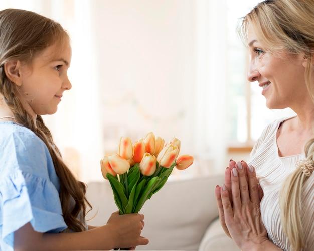 Filha dando buquê de tulipas para a mãe