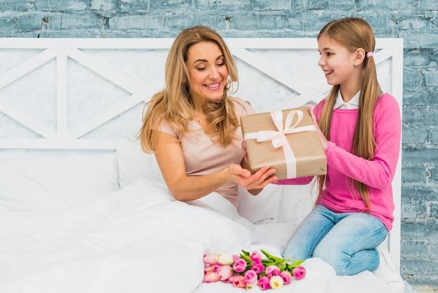 Filha dando caixa de presente para a mãe na cama
