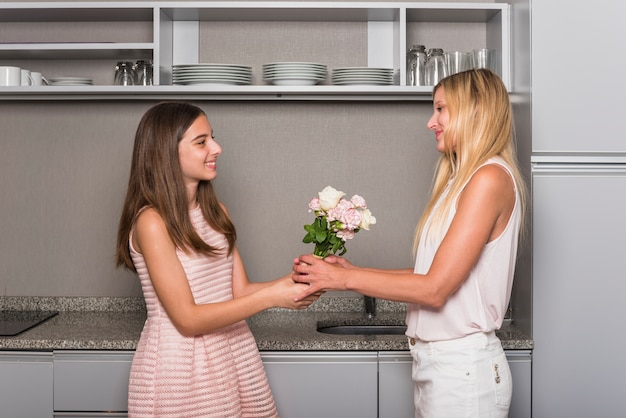 Filha dando flores para a mãe na cozinha