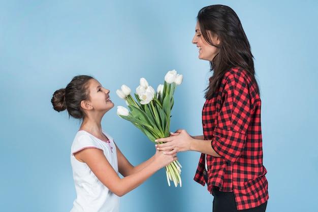 Filha dando tulipas brancas para mãe