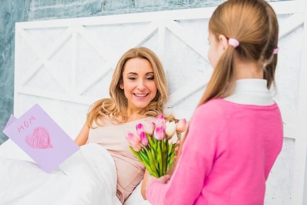 Filha dando tulipas para a mãe na cama