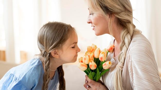 Filha dando um buquê de tulipas para a mãe como presente