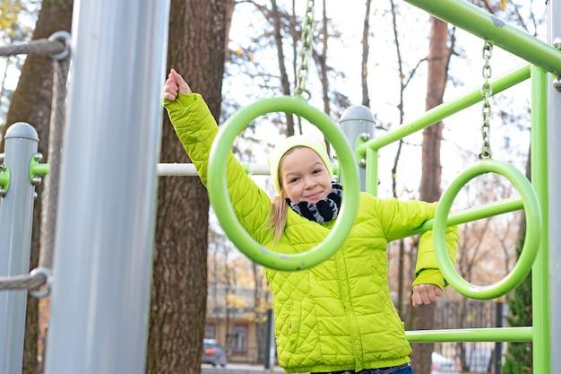 Filha de adolescente linda em uma jaqueta verde plaing no playground do esporte no parque outono.