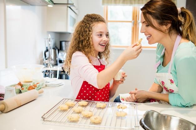 Filha de alimentação cookies para sua mãe na cozinha