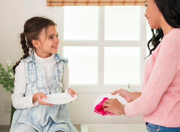 Filha de alto ângulo, ajudando a mãe com a limpeza