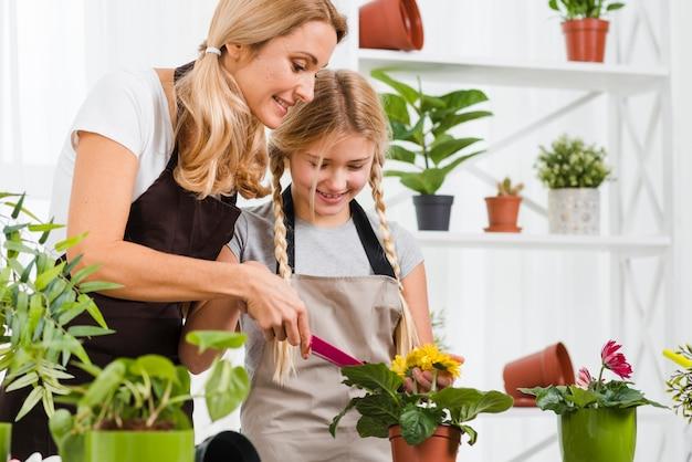 Filha de alto ângulo, ajudando a mãe em estufa
