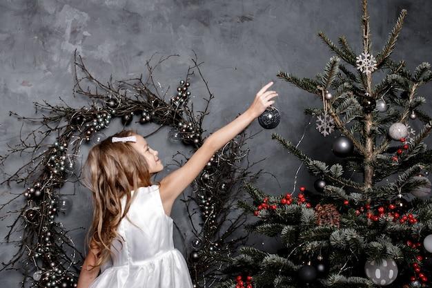 Filha de criança decorar a árvore de natal em casa.