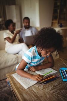 Filha de desenho no livro enquanto os pais usando o laptop no fundo