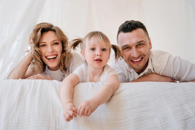 Filha de garoto bonito e pai fazendo cócegas mãe se divertindo bom tempo jogando juntos em casa, pais felizes e menina criança desfrutando de atividade e comunicação engraçadas, família rindo relaxante